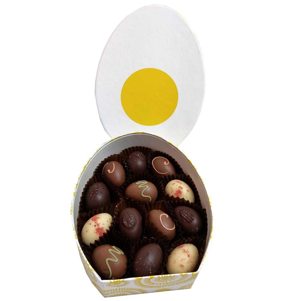 Scatola dell'uovo di Pasqua riempita di praline dell'uovo di Pasqua del cioccolato fresco